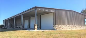 40' x 80' x 14' metal constructed shop/living quarters with 3 bays and 4ft of stone