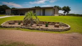 Custom built barndominum with 2 large doors and custom landscaping