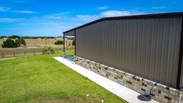 Side view of the custom built barndominum with custom stone work