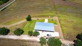 Drone picture of a custom built barndominum with 2 large doors and custom landscaping