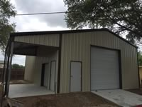 Custom built metal building with a lean to and roll up door on the end