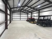 Interior view of a finished out metal building with tractor and side by side